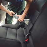 Car care concept, detailing and cleaning of interior back seats at luxury modern cars